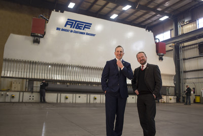 Ken Ripich (left) and Michael Forde Ripich stand in front of a 2,800-ton, 60-foot single ram press brake, which is representative of the heavy-duty equipment that AT&F is known for.