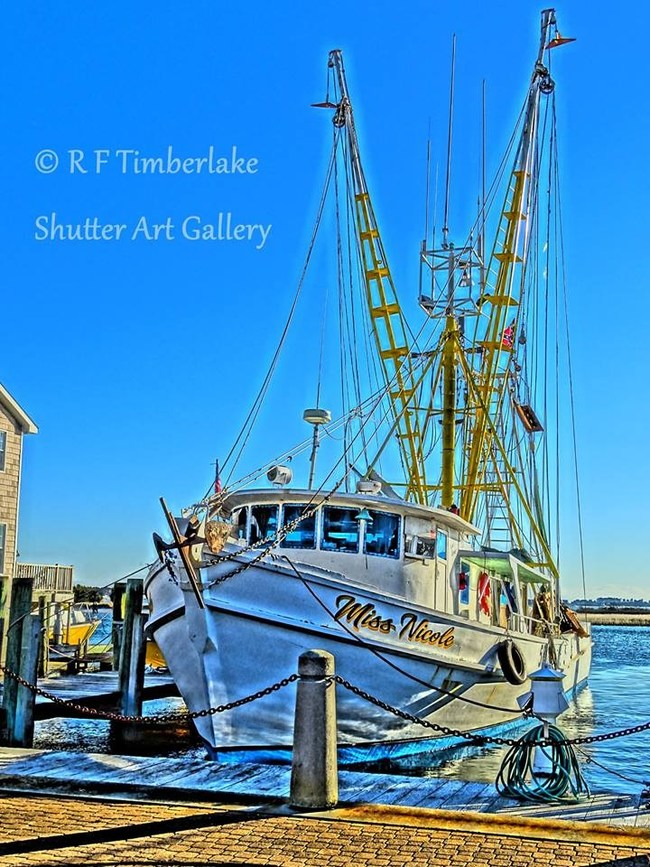 Miss Nicole limped in, the first shrimp trawler to dock in Morehead City, NC loaded with thousands of pounds of shrimp in January. R F Timberlake caught her on a cold January day while mechanics worked on her engine and pumps, and while workers unloaded her bounty. Timberlake photographed the trawler in 20-degree weather and then made his digital fine art print.