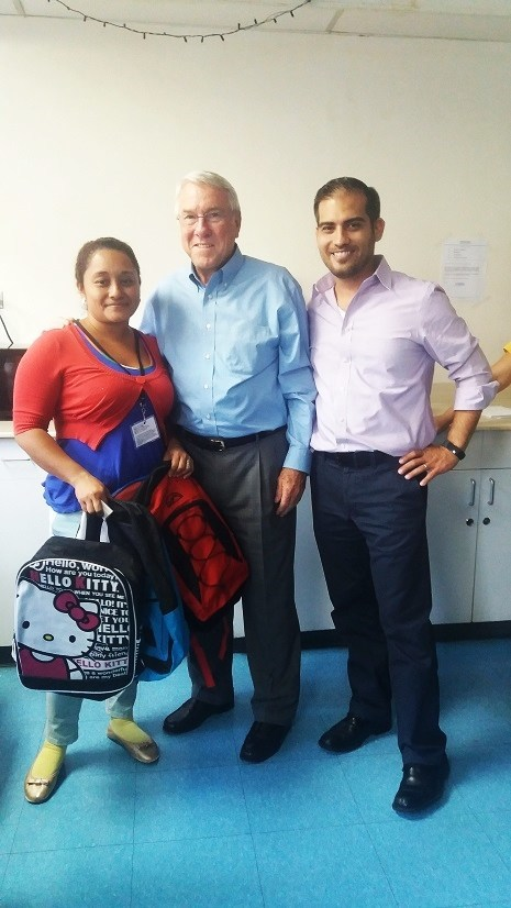 Founder and CEO of Command Medical Products, David Slick, Sr. joins Managua plant manager Carlos Gadea in presenting Belky Garcia with three free backpacks for her children. Belky was one of the many recipients of the 155 backpacks filled with school supplies provided to Command Medical Products' employees in January 2017.