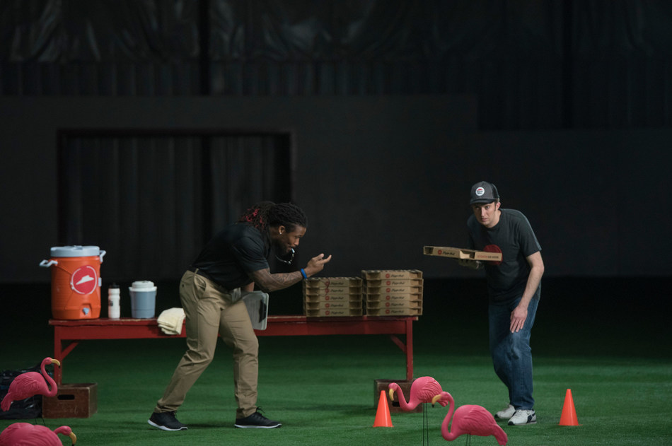 Professional football running back DeAngelo Williams (left) trains a delivery rookie (right) at the Pizza Hut Delivery Combine, in advance of the Big Game - the restaurant company's busiest day of the year. (AP Images for Pizza Hut)
