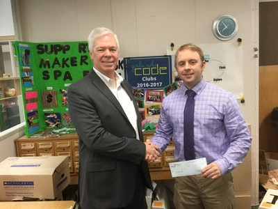 Mike Wilke (pictured left), founder and CEO of Wilke Global, presents a check to Mark Briggs (right), teacher at Davis Middle School.