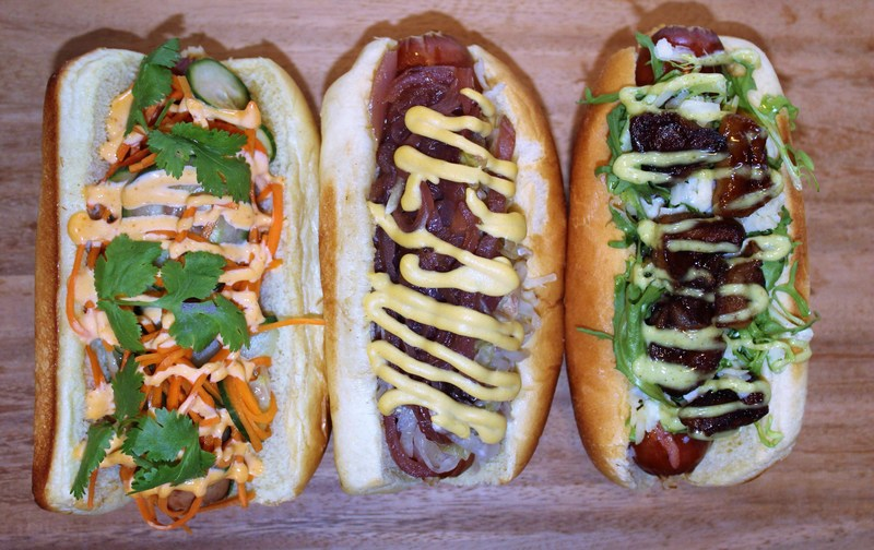 Three of Kings of Kobe's delectable dogs: the Banh Mine, marinated cucumbers and carrots, cilantro, sriracha aioli; King's Classic, red onion marmalade, sauerkraut, yellow mustard; and Manhattanite, wasabi aioli, caramelized apples, frisee, shaved cheddar.
