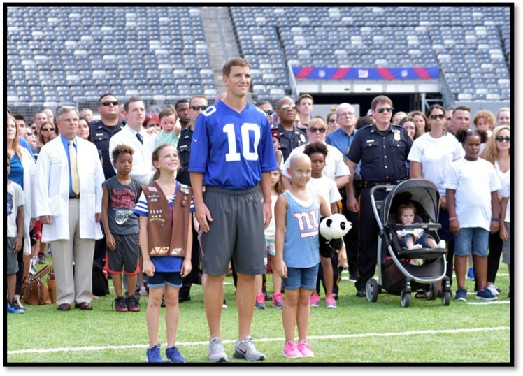 New York Giants Quarterback Eli Manning stands with doctors, nurses, team members, patients and families from Hackensack University Medical Center as a part of the Tackle Kids Cancer campaign.  Since volunteering to champion the Tackle Kids Cancer campaign ahead of the 2015 season, Eli Manning regularly visits the children battling cancer at the Children's Cancer Institute at HackensackUMC.  His fundraising, appearances and personal donations have directly led to more than $1,000,000 in fundraising in just over one year, and propelled the new charitable program to over $4,000,000 in funds raised since its inception.