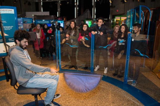 "With his classmates watching on, a student from Marc Garneau Collegiate Institute tries to ""fly"" by testing the difference between short and long wings at the Ontario Science Centre's new exhibition Biomechanics: The Machine Inside. This family-friendly, interactive exhibition, which brings the science of biomechanics to life, opened today and runs to May 7, 2017. (CNW Group/Ontario Science Centre)"