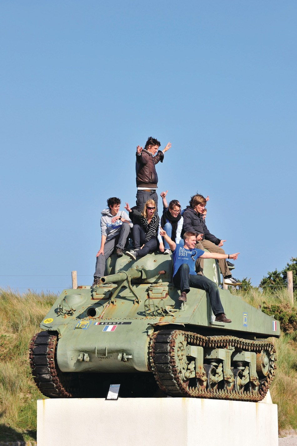 Teenagers on World War II American Sherman Tank near Utah Beach, Normandy, France.