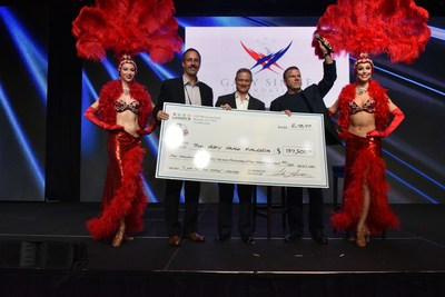 Tilman Fertitta, CEO of Landry's, Inc., and Senior Vice President and COO of Bubba Gump Shrimp Co. Jim Dufault, present $137,500 check to the Gary Sinise Foundation on-stage at the Landry's Leadership Conference on February 8, 2017.