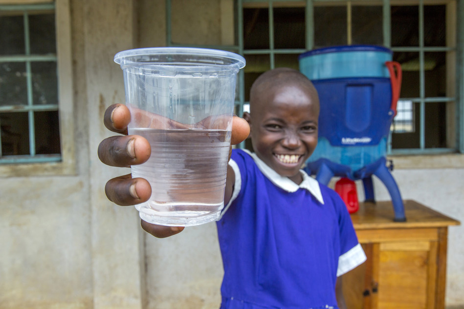 Girl at school in rural Kenya proudly shows the glass of water she poured from the LifeStraw Community water purifier which transforms microbiologically contaminated water into safe drinking water.