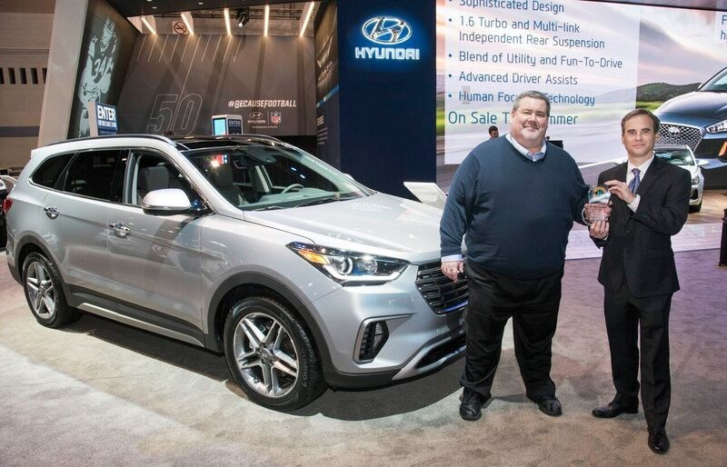 Scott Margason, director, product planning, Hyundai Motor America accepts the 2017 Consumer Guide Automotive Best Buy Award trophy for the 2017 Hyundai Santa Fe and Santa Fe Sport from Tom Appel, publisher, Consumer Guide Automotive.