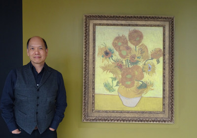 "Vancouver art gallery owner Ian Tan admires Van Gogh ""Sunflower"" painting."