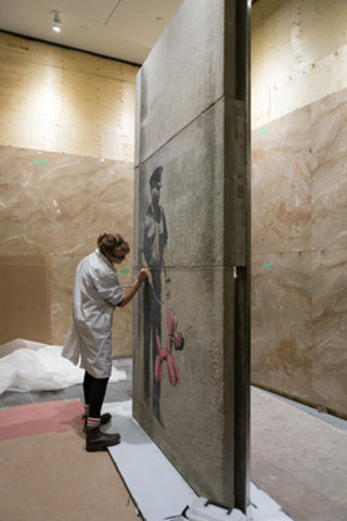 Assistant conservator of CSMO Emily Ricketts applies finishing touches to the Banksy installation in the PATH system at One York Street.  (Image supplied by Menkes Developments; Photo by Paul Casselman) (CNW Group/Menkes Developments Ltd.)