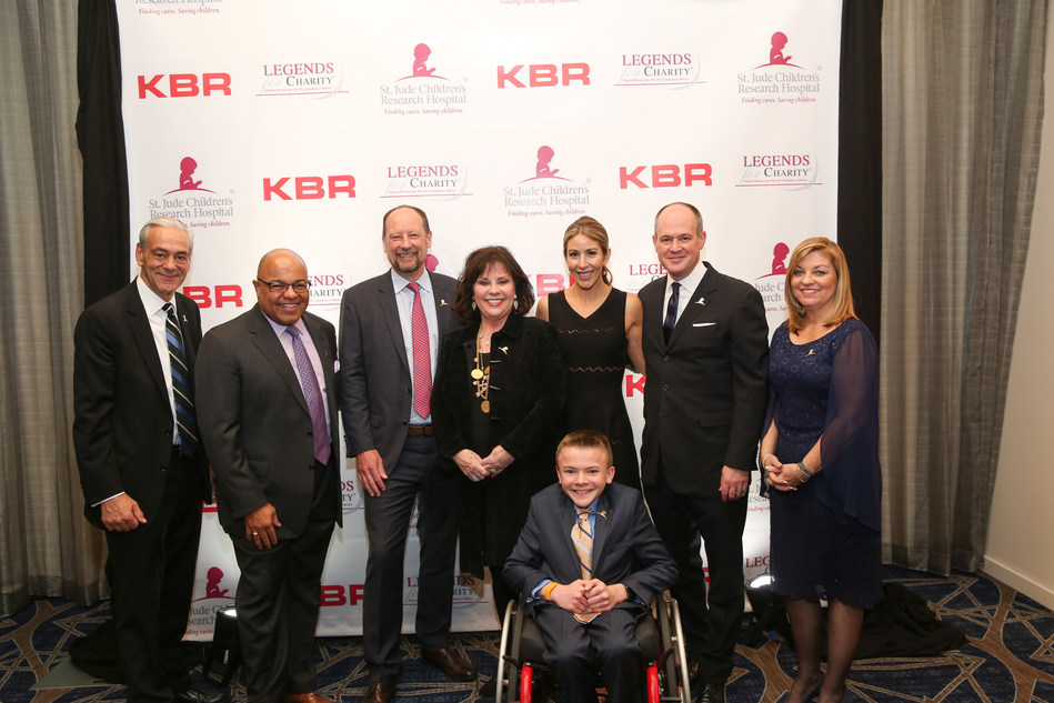 L-R: Richard Shadyac, Jr., President and CEO of ALSAC, the fundraising and awareness organization for St. Jude Children's Research Hospital; Mike Tirico, NBS Sports; Stuart Braddie, KBR Inc. President & CEO; Cheri Summerall, wife of belated Pat Summerall; Suzy Shuster, wife of Rich Eisen; Rich Eisen, NFL Network and award honoree; Cheryl DeLeonardis, Ocean 2 Ocean Productions and Event Producer; (front row)  St. Jude patient Austin. Photo credit: Ashkan Image