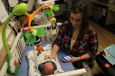 "Stephanie Lipstein listens to Hand to Hold's new ""NICU Now"" podcast while bedside in a hospital neonatal intensive care unit next to her son Kyler, a surviving twin who was born premature at 24 weeks, five days, weighing 1 lb. 9 oz. and was 12 1/2 inches long."