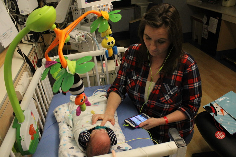 """Stephanie Lipstein listens to Hand to Hold's new """"NICU Now"""" podcast while bedside in a hospital neonatal intensive care unit next to her son Kyler, a surviving twin who was born premature at 24 weeks, five days, weighing 1 lb. 9 oz. and was 12 1/2 inches long."""
