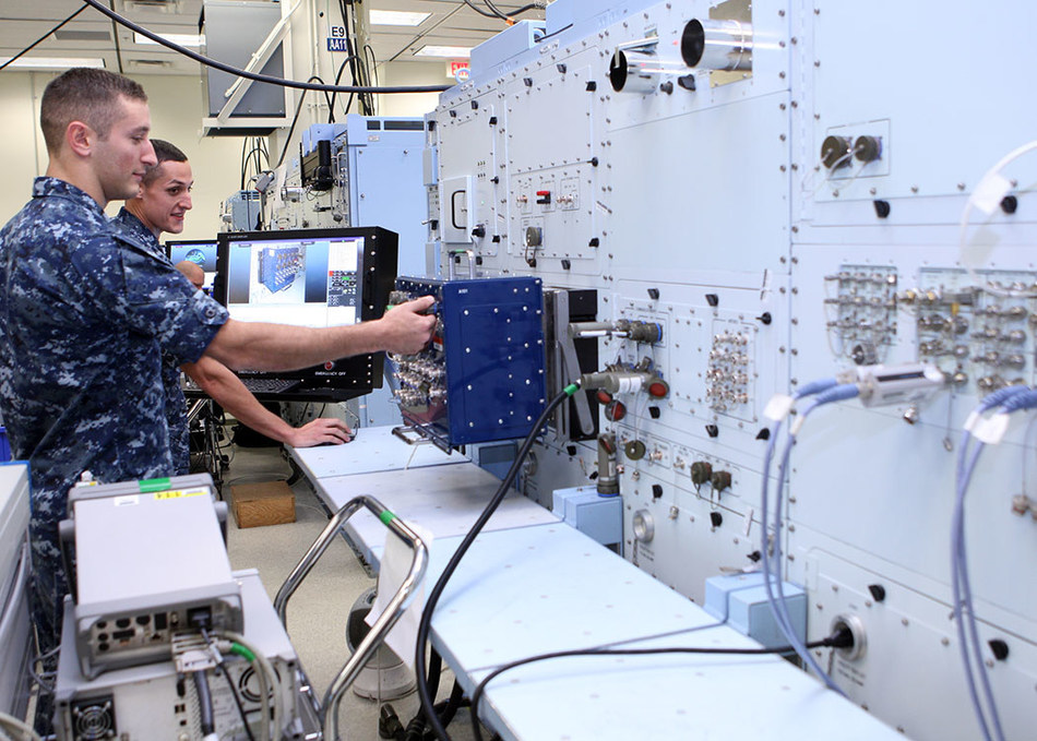 Petty Officers Third Class Ira Schwartz (left) and Devin Riley, both aviation electronics technicians, perform diagnostic tests on the U.S. Navy's electronic Consolidated Automated Support System (eCASS) at Lockheed Martin's Rotary and Mission Systems site in Orlando, Fla. eCASS will enable a cost avoidance of more than $1 billion annually by repairing avionics at operational locations, averting repair at the next level of maintenance or sending parts to the original equipment manufacturer.