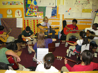 Students learn to play electric and acoustic guitar with their music teacher.