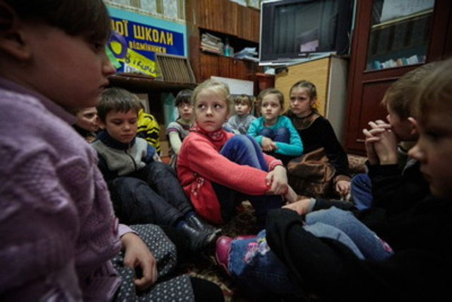 On February 13, 2017, first grade students, including six-year-old Sasha (in red sweater), hide during shelling in a part of the school building with strong walls. The school does not have a basement which can be used as a bomb shelter. Sasha's house is located some 15 kilometers from the contact line in Toretsk, Donetsk Region, Ukraine. Sasha and her sister, Diana, have been living with their grandmother in this house since the beginning of the conflict in 2014 while their parents live in Donetsk city where they work. © UNICEF/UN053119/Zmey (CNW Group/UNICEF Canada)