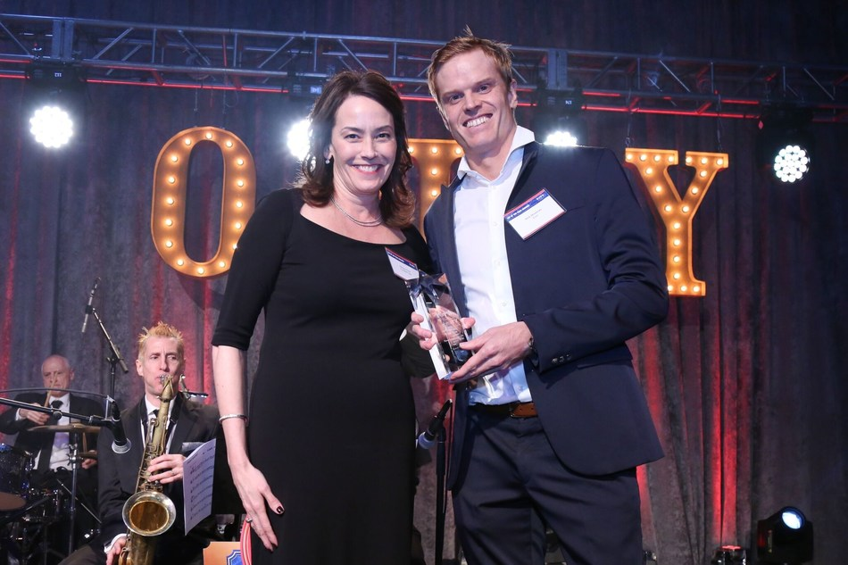 Nick Mowbray, President of ZURU, accepts the Outdoor Toy of the Year (TOTY) award for Bunch O Balloons at the Toy Industry Association's Annual Toy Of The Year Awards gala from Shirley Price, TOTY Committee Chair and COO of Funrise.