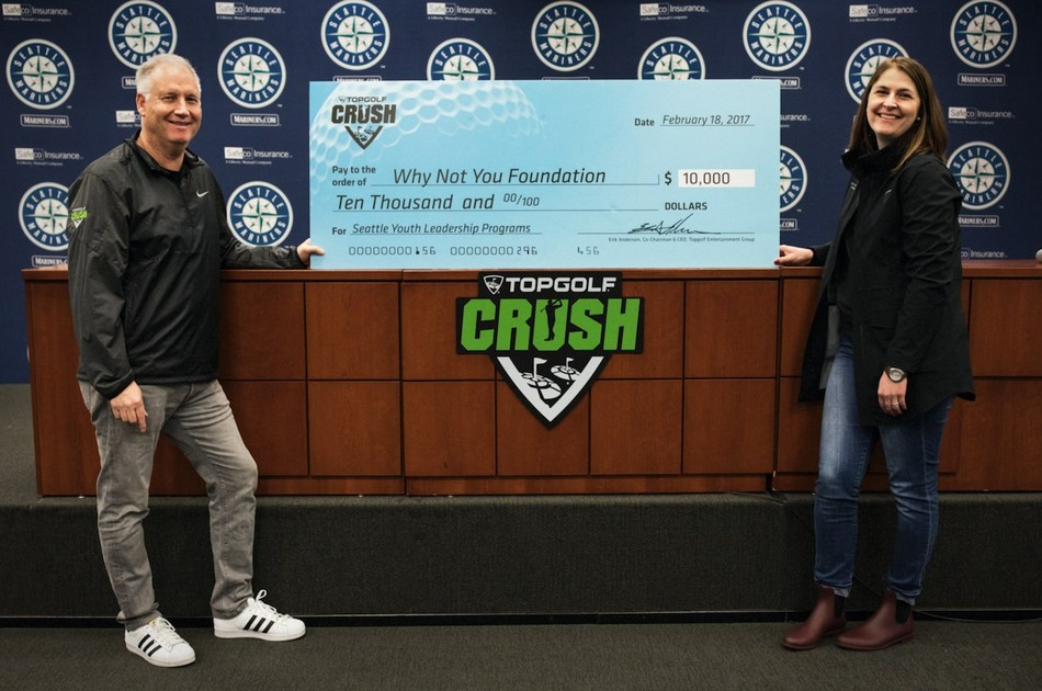 Topgolf Entertainment Group Co-Chairman and CEO Erik Anderson presents Why Not You Foundation Executive Director Carly Young with $10,000 check to support Seattle youth.