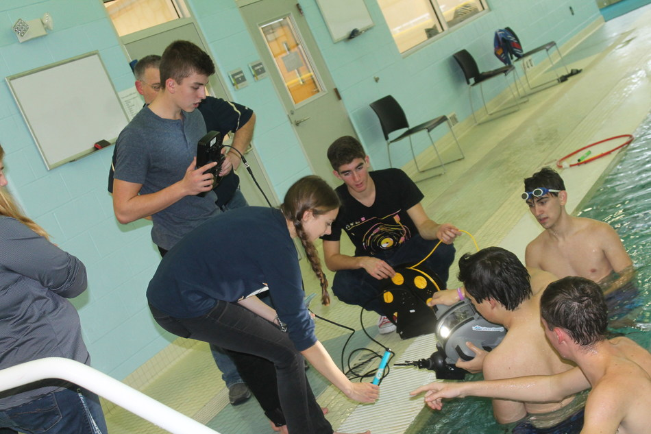 Students calibrate the remote control with the ROV. Students on deck (left to right): Luke Pawlak, Sarah Hagen and Jack Lindsey; students in water (left to right): Damian Kowalczyk, Adam Popper and Chris Diviero.