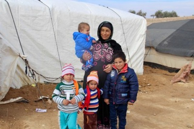 Syrian refugee Sara, second from right, holds her son Ahmed, 1, as she stands with her daughters Hanan, 4, left, Fatima, 3, second from left, and son Ali, 5, right, as they wear new winter clothes distributed by UNICEF at an informal tented settlement near Mafraq, Jordan, Wednesday, 21 December, 2016.   UNICEF aims to reach 150,000 disadvantaged children living in Syrian refugee camps, host communities and other difficult locations across Jordan with assistance this winter.  UNICEF's 2016/2017 winter assistance programme in Jordan is helping thousands of vulnerable Syrian refugee families protect their children from the cold. With temperatures dropping close to freezing in many parts of country, UNICEF is using a mixed strategy of cash support and in-kind distribution to urgently support over 150,000 disadvantaged children living in refugee camps, host communities and other difficult. As of December 2016, all children in Za'atari and Azraq refugee camps, over 60,000, are receiving a one-time cash grant of 20 Jordanian Dinars (~USD28) per child. UNICEF is supporting the Norwegian Refugee Council to distribute the cash directly to the heads of households. In addition, over 25,000 of the most vulnerable children in host communities are also receiving a similar winter cash assistance from UNICEF. Families are being informed through mobile text messages, posters, flyers and awareness sessions that the UNICEF cash assistance is for the winter needs of their children. Outside camps, in areas with limited access to the market, and to families encamped at Jordan's northeastern border, UNICEF is delivering winter kits to more than 65,000 children through partners. (CNW Group/UNICEF Canada)