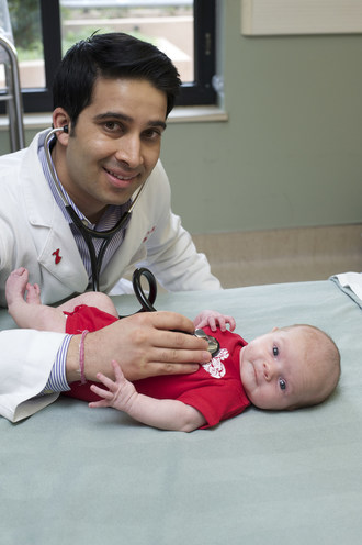 Nikhil Daga, MD, board-certified interventional cardiologist, Huntington Hospital in Pasadena, California, is pictured with newborn Olivia, highlighting the importance of heart health, even at the first moments of life.