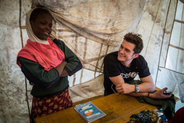 "UNICEF Goodwill Ambassador Orlando Bloom (right) smiles as he listens to twelve-year-old Aicha Gabtchami, a fifth grade student, speak at a temporary learning space at a camp for internally displaced people in Ngagam, near Diffa, Niger, Friday 17 February 2017. Aicha, who was displaced from Barwa, Niger near Lake Chad, came to Ngagam camp with her mother and grandmother by foot. The family were forced to flee after being threatened by Boko Haram members, who killed other people around them as they fled. Her uncle was killed while in the bush. Aicha's father, who had already left Barwa, was also killed by Boko Haram insurgents. Attending classes at the school makes Aicha feel better, ""more comfortable"" as she puts it. (CNW Group/UNICEF Canada)"