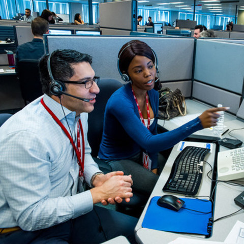Ferio Pugliese, Executive Vice President of Customer Care and Corporate Affairs at Hydro One sits with a Customer Call Centre representative to talk to customers about their concerns.  The Company is changing the way it does business and Hydro One Day was about listening and speaking directly to their customers. (CNW Group/Hydro One Inc.)