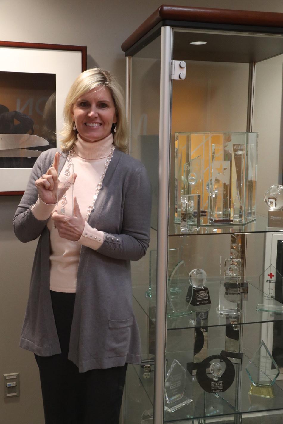 Cartus Training Manager, Kathleen Mulvihill, proudly holding a trophy awarded by Training Magazine