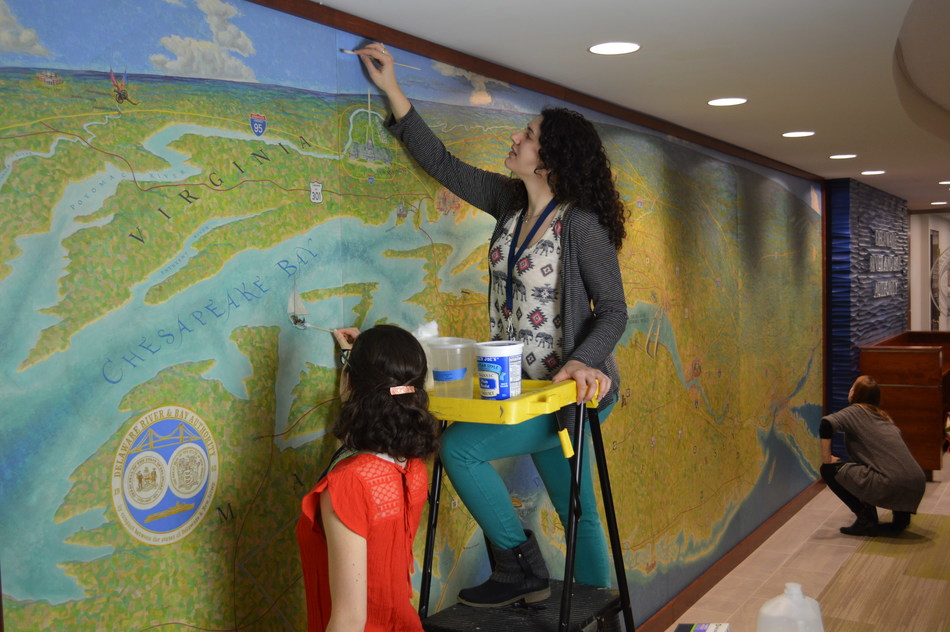 """On February 24, Amanda Kasman (left) and Karissa Muratore began the restoration process on the """"Micarta"""" East Coast Mural located in the lobby of the Delaware River and Bay Authority's administration building in New Castle, Delaware. The work is expected to take approximately six weeks to complete.  Dr. Kristin deGhetaldi (kneeling in background) is supervising the project."""
