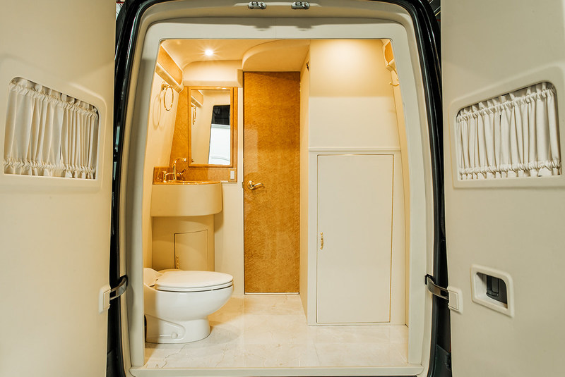 Gold-plated lavatory area with coat rack.