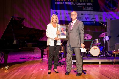 """Shelton G. 'Shelly"""" Berg, Dean at the University of Miami Frost School of Music presents Canon Solutions America's Valerie Belli with a plaque for their support of the Dizzy Gillespie Tribute."""