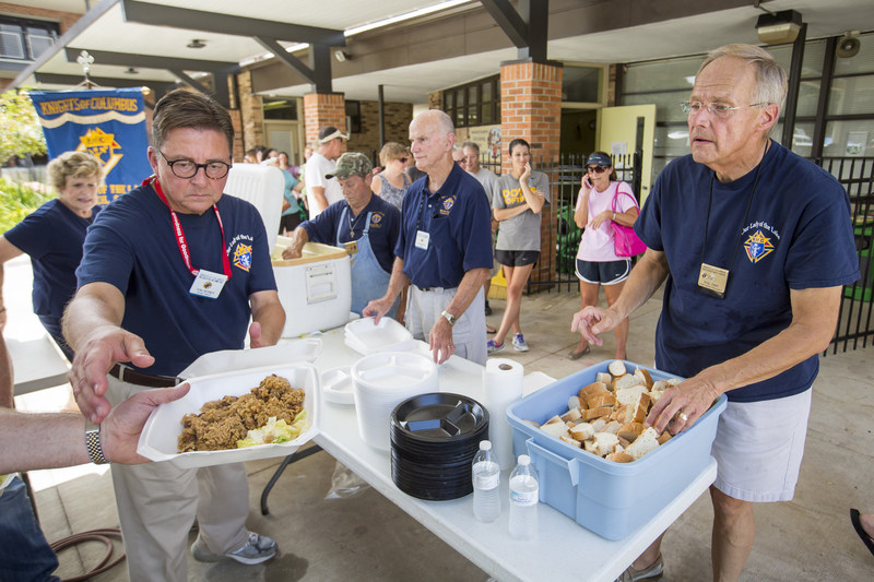 Grand Knight Tom Berner (left) and Phil Zima (right) of Our Lady of the Lake Council 9240 in Mandeville, La., serve jambalaya meals to volunteers and victims of the August flooding. Knights are performing similar actions in the wake of the recent tornadoes in the New Orleans area.