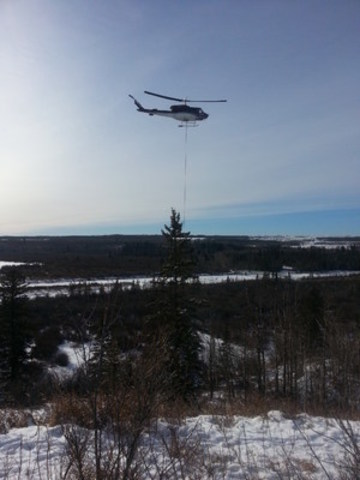 A Bell 212 deploys seismic equipment via long line on an Explor high-definition 3D seismic survey in northern Alberta in January 2016.  (Photo credit: Paul Thacker) (CNW Group/Explor)