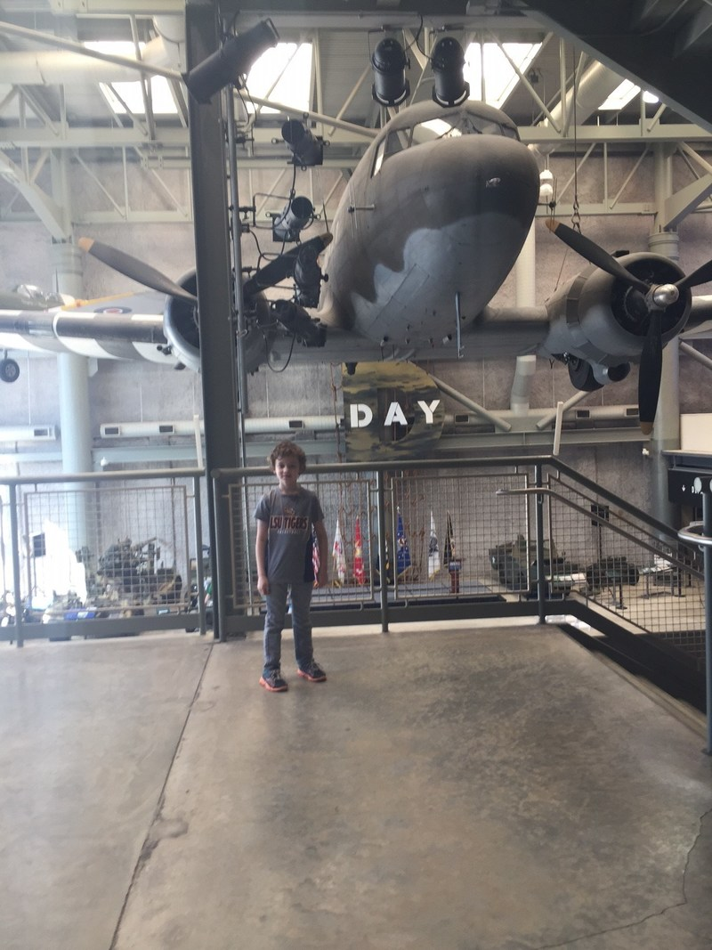 Wounded Warrior Project supporter Hunter poses in front of an airplane at a military history museum.