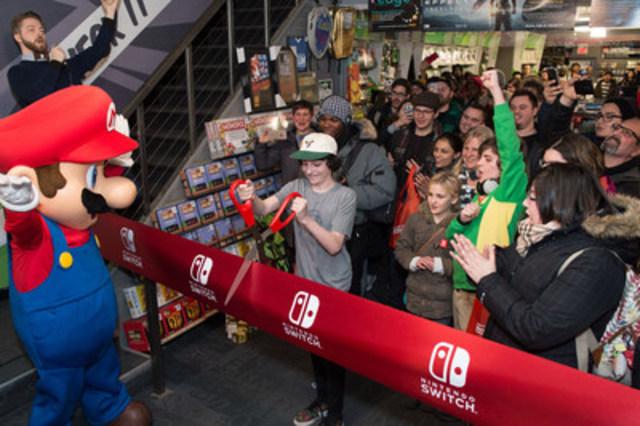 L'acteur canadien Finn Wolfhard, célèbre pour son rôle dans Stranger Things sur Netflix, avec Mario et plusieurs fans au lancement de la Nintendo Switch à Toronto le 3 mars 2017 à minuit. La Nintendo Switch peut changer d'une console de salon à une console portable en un tour de main. (Groupe CNW/Nintendo of Canada)