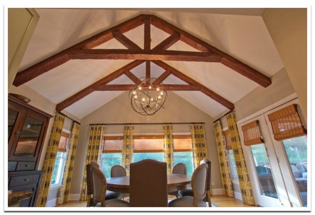 Custom Timber beams from FauxWoodBeams.com are ideal for building decorative trusses. Their look of natural wood adds warm character to this dining room.