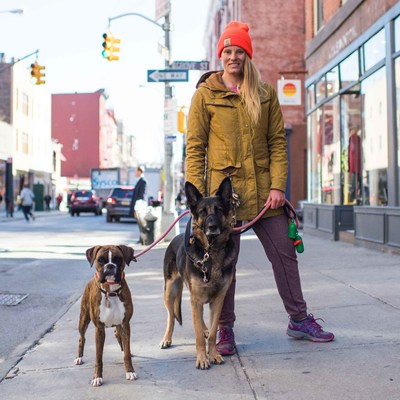 """Ann-Cristin and Penelope & Gunther, German Shepherd and Boxer (2 y/o and 2 y/o)  """"Being a dog walker keeps me sane,"""" Ann-Cristin says. """"It combines the three things I need in life: being outdoors, being active, and being with animals."""" Ann-Cristin walks more than 20 dogs, and loves it because of the way dogs give back to you. """"Just like how children frustrate parents, dogs can do that, too,"""" Ann-Cristin says. """"But they offer the same unconditional love."""""""