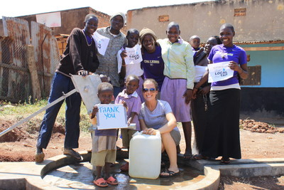 Erin Huber, founder and executive director of Drink Local, Drink Tap, celebrates with children in Uganda who now have access to safe, clean water.