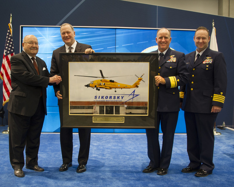 Sergei Sikorsky (left) and Sikorsky President Dan Schultz present U.S. Coast Guard aviators Rear Adm. David Callahan and Capt. Joe Kimball with a framed photo of an MH-60T Jayhawk helicopter taking off from Sikorsky's Stratford, Connecticut headquarters on Dec. 7, 2016. The aircraft is painted chrome yellow to commemorate the U.S. Coast Guard's aviation centennial (1916-2016).