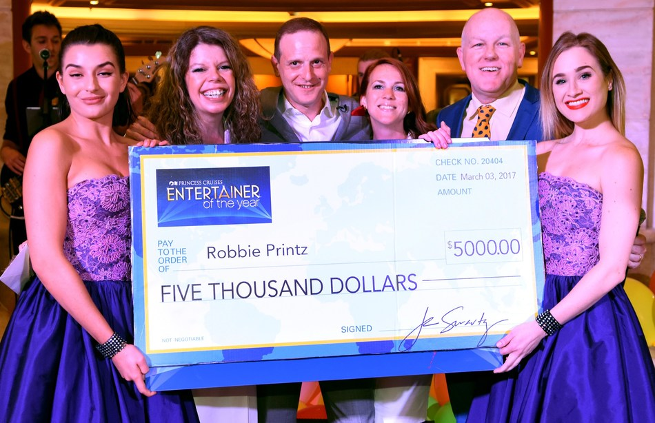 Robbie Printz, voted 2016 Entertainer of the Year by Princess Cruises guests. Cruise Director Paul Burns and members of the Ruby Princess entertainment staff were on-hand to present the check.