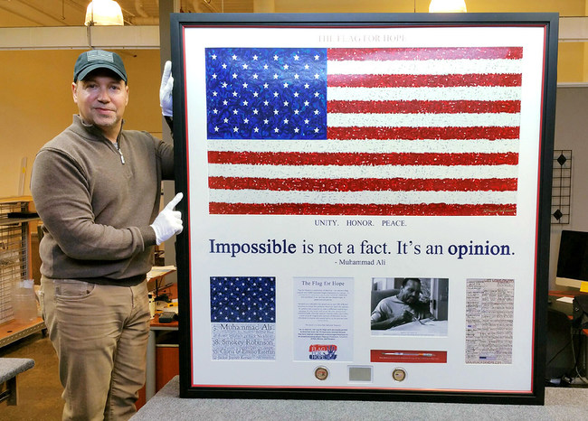 Chris Cavedon, Flag for Hope CEO, stands with the shadowbox commemorating Muhammad Ali's participation at Star #3