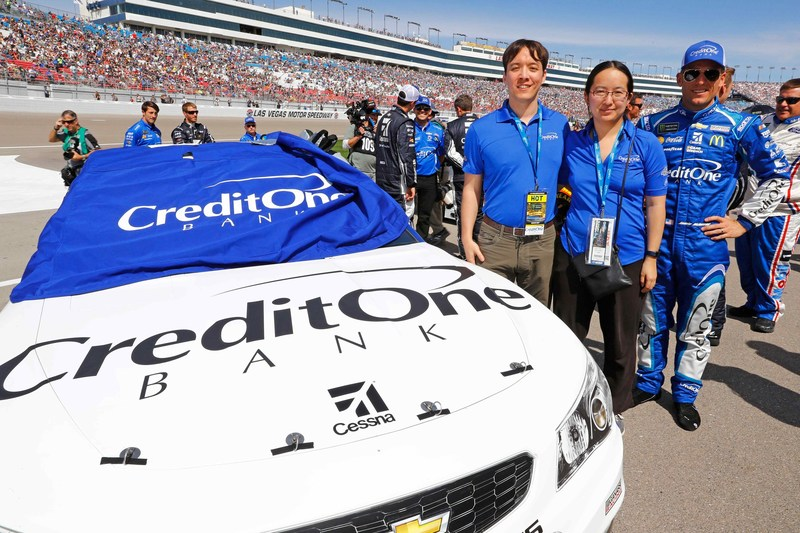 NASCAR fan Aaron and his wife, the winners of the Credit One Bank Ultimate Race Weekend sweepstakes, pose with Jamie McMurray, driver of the No. 1 Chevrolet at the Kobalt 400 in Las Vegas.