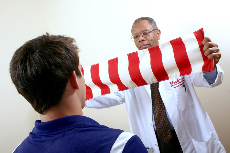 HeadFirst Sports Injury and Concussion Care's Stanford Coleman, MD, moves a striped cloth known as an optokinectic nystagmus strip in front of a head trauma patient. This test checks reflexive eye movement to detect the presence of optokinetic nystagmus (OKN), which shows as slowness or inaccuracies in the ability to follow a visual target. The OKN strip is one of several tests administered at HeadFirst Concussion Centers in the case of a suspected concussion.