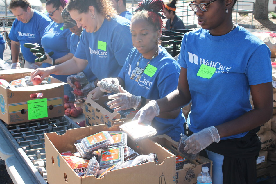 WellCare volunteers pack boxes at a March 11 mobile food pantry hosted by Feeding Tampa Bay at the George A. Bartholomew North Tampa Community Center in Tampa, Fla.
