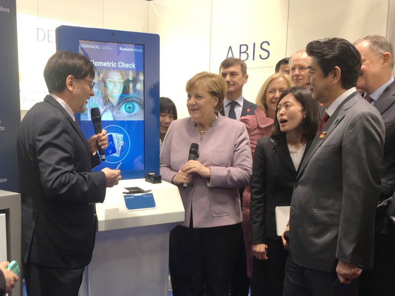 DERMALOG´s CEO Gunther Mull presents multi-biometric solutions to Chancellor Dr. Angela Merkel and to Prime Minister Shinzo Abe, at the company's CeBIT stand. (PRNewsFoto/Dermalog Identification Systems)