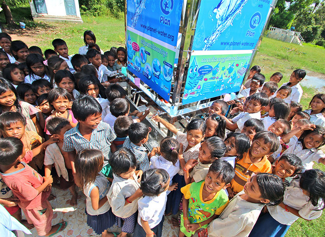 Children in rural Siem Reap, Cambodia gather around the Planet Water AquaTower; their source of clean, safe drinking water and hand washing.