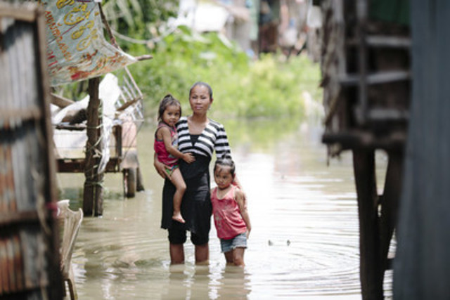 Srey Nuch, 31, with her two young daughters in the Chong Kaosou community, Siem Reap, Cambodia. Srey Nuch fears that her children could drown in filthy flood waters when she is out working. Credit: WaterAid/Tom Greenwood (CNW Group/WaterAid Canada)