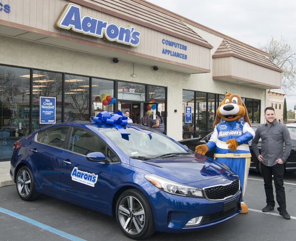 """Aaron's, Inc., a leader in the sales and lease ownership and specialty retailing of furniture, consumer electronics, home appliances and accessories, delivered a brand new 2017 blue Kia Forte EX wrapped in a big blue bow to Adam Barbour of Stockton, CA, the grand prize winner of Aaron's """"Big Blue Bow Event,"""" at the Aaron's store in Tracy, California. Aaron's offers shoppers great lease-to-own deals with flexible payment options, no credit needed and the opportunity to pay off early and save."""