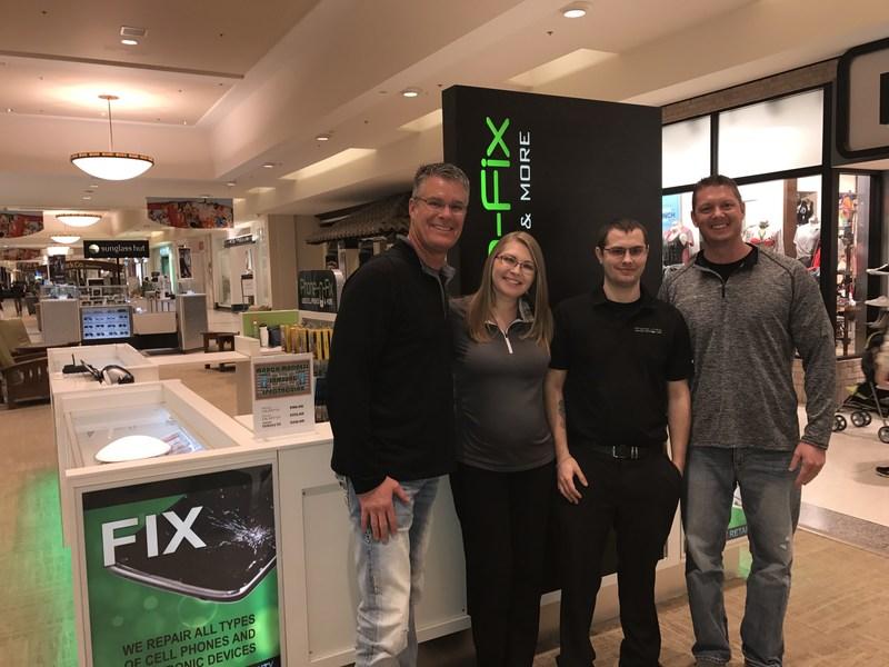 Steve Michael, Miranda and Carl Burfeind, and TJ Barthman celebrate the grand opening of Phone-n-Fix West Acres Mall in Fargo, North Dakota