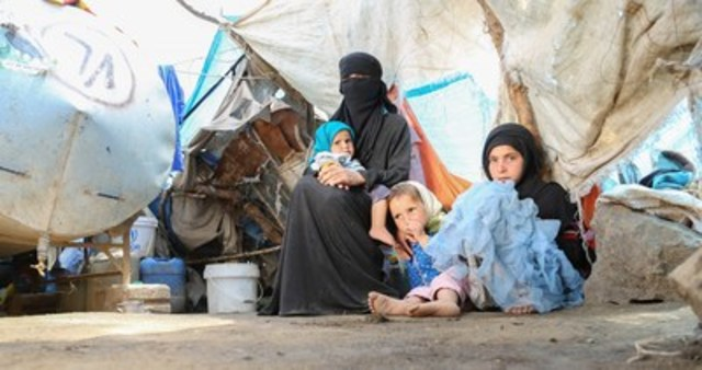 A displaced Yemeni woman sits with her daughters at their temporary home in a camp. Photo: UNICEF/Al-Zikri (CNW Group/UNICEF Canada)